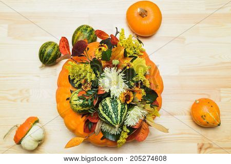 autumn bouquet of decorative pumpkins flowers and leaves in a vase of orange pumpkin on a wooden table