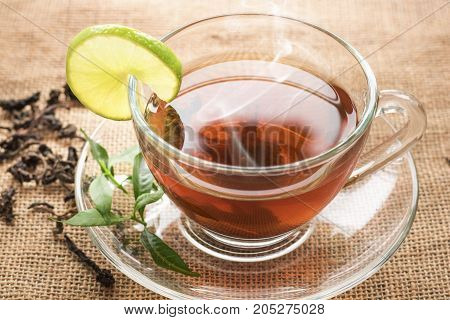 Hot tea of cup with slice of lemon on hemp sack for break fast and drinking time in morning