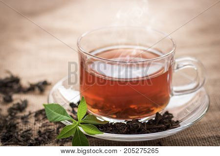 Hot cup of tea for break time on hemp sack background in vintage style in morning
