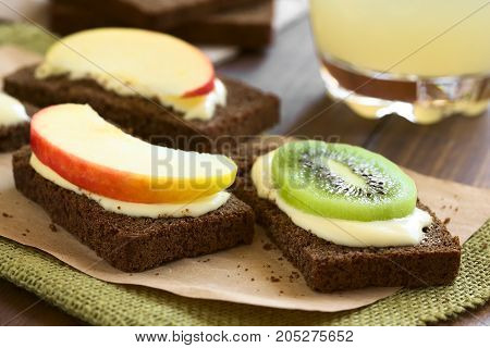 Wholegrain bread sandwiches with cream cheese and fresh apple or kiwi slices photographed with natural light (Selective Focus Focus on the front of the kiwi and apple slices on the first sandwiches)