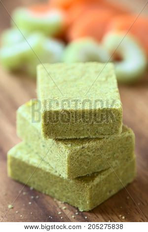 Vegetable bouillon stock or broth cubes on wooden plate with fresh celery and carrot in the back photographed with natural light (Selective Focus Focus on the upper front edge of the top cube and the front upper corner of the middle one)