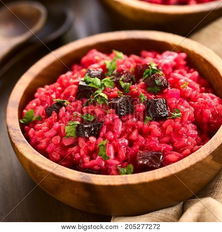 Beetroot risotto prepared with beetroot puree roasted beetroot pieces and parsley on the top photographed with natural light (Selective Focus Focus in the middle of the risotto)