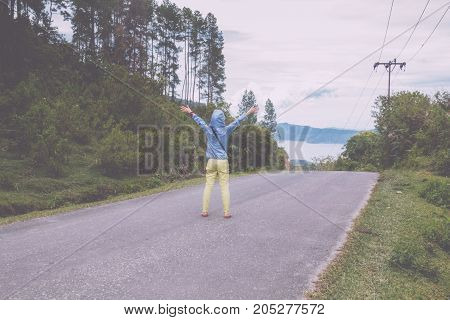 woman standing on road looking at the lake toba