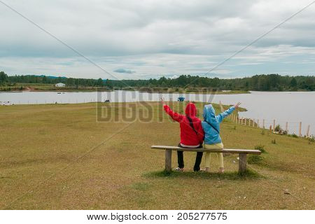 Couple siting on chair looking at the lake