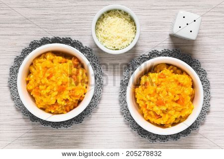 Fresh homemade carrot risotto made with pureed carrot and roasted carrot pieces served in bowls photographed overhead with natural light (Selective Focus Focus on the top of the risotto)