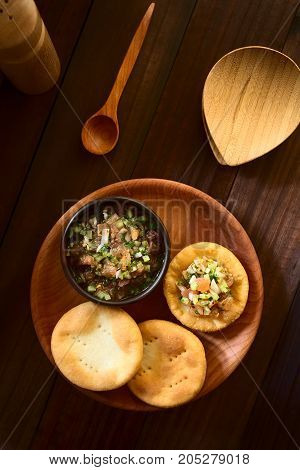 Traditional Chilean Sopaipilla fried pastries made of a bread-like leavened dough served with a bowl of Chilean pebre salsa on the side photographed overhead on dark wood with natural light