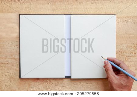 male hand with spring shirt writing something with pencil on blank paper put on wooden tabletop use for texts display