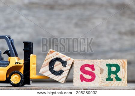 Yellow plastic forklift hold letter C to complete word CSR (Abbreviation from corporate social responsibility) on wood background
