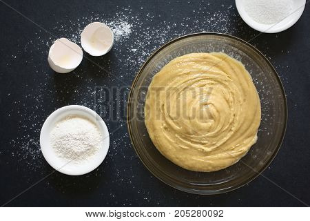 Basic homemade cake or cookie dough in glass bowl with ingredients on the side photographed overhead on slate with natural light (Selective Focus Focus on the dough)