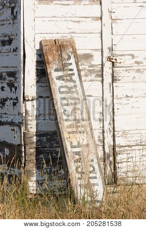 Portion of a weathered old building with a painted sign for Home Insurance.