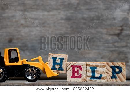 Yellow plastic bulldozer hold letter H to complete word help on wood background