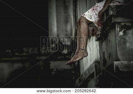Zombie woman sitting on the edge of the window in an abandoned building on Halloween. Women dressed in zombie