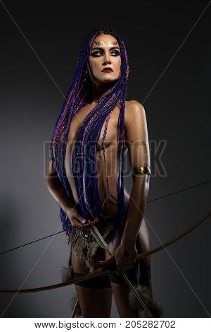 Sexy resolute horsewoman with African blue braids hairstyle, temporary gold tattoo on her face and bright makeup topless holding bow and arrows in her hands portrait