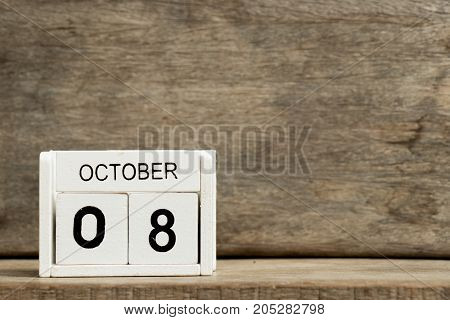 White block calendar present date 8 and month October on wood background