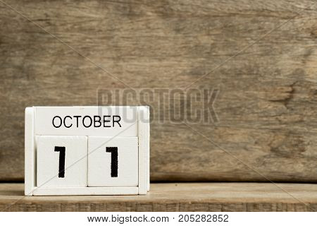 White block calendar present date 11 and month October on wood background