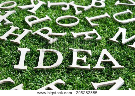 Wood alphabet in wording Idea on artificial green grass with another letter background