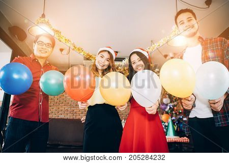 Asians people are together to celebrate the Christmas and Happy New Year party. They holding the ballons.