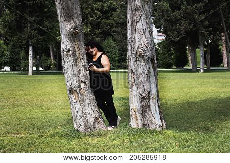 Woman talking on mobile phone in nature on a summer morning