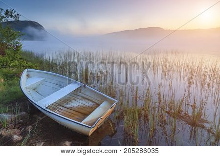 Boat on the shore of a misty lake on a summer morning.