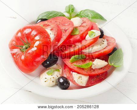 Tomato And Mozzarella Slices With Basil Leaves On A White Plate.