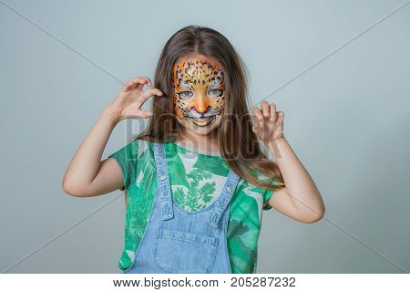beautiful girl with a tiger painted on his face on a gray background