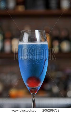 blue alcoholic cocktail and cherry in a bar