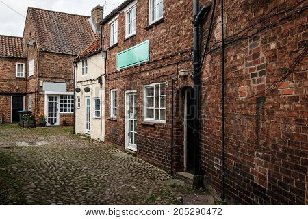 Dark Brick Houses And Cobblestones In The Old City Thirsk, North Yorkshire, England, Uk