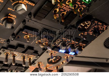 Detailed view of the upper set of switches in a large airliner. Selective focus. Low Light from a plane control cockpit in the dark vintage detail on the interior cockpit