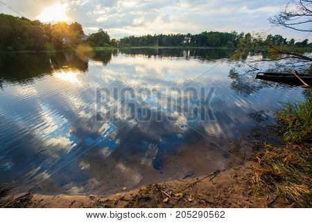 the sunset on the lake with patches of sunlight and clouds reflected in the water