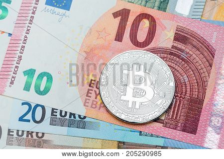 Close up of silver Bitcoin on euro currency background. Macro photo. High resolution photo.