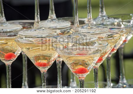 A slide of champagne. Pyramid at the wedding of champagne glasses with red cherries.