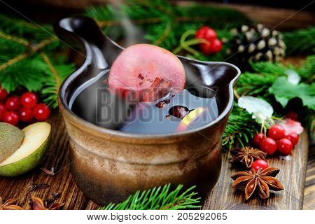 mulled wine in a saucepan with pear and rose hips