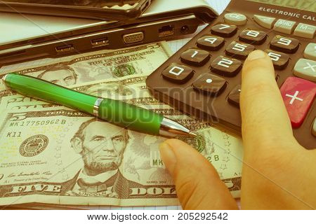 Calculator and money on wooden table. The concept of financial planning savings. Business Objects in the office on the table calculator and money on table - Retro color
