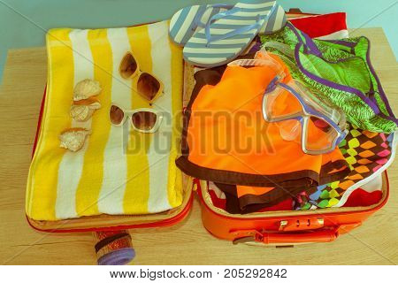 Anticipation of voyage. Women's clothes and accessories in black suitcase. Open suitcase packed for travelling - Retro color