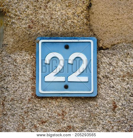House number twenty two (22) on a stone wall.