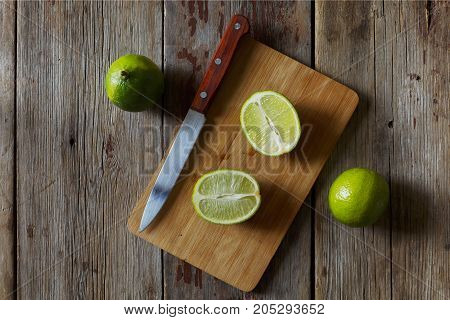 Fresh Lime Whole And Cut Into Pieces On A Wooden Table. Rural Style Closeup.
