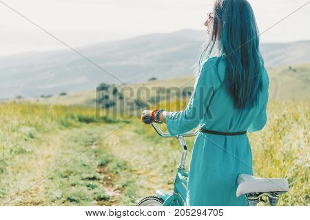 Fashionable young woman wearing in blue dress standing with bicycle on summer meadow.