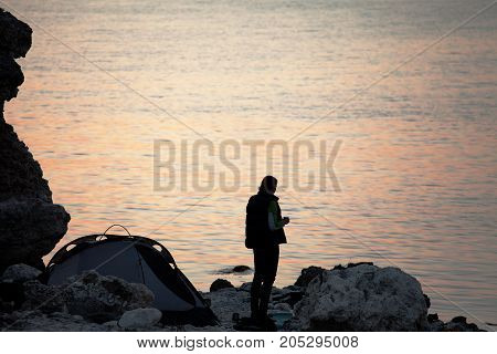 Girl with cup of tea on rocky seashore near camping tent at summer evening