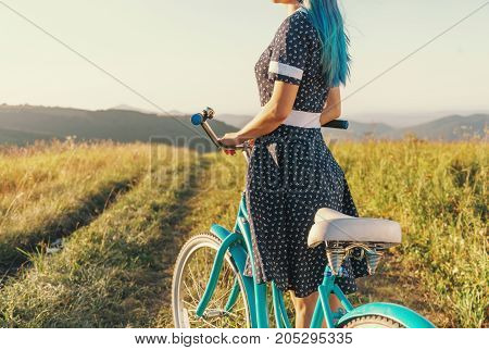 Unrecognizable young woman wearing in dress standing with bicycle cruiser on summer meadow.