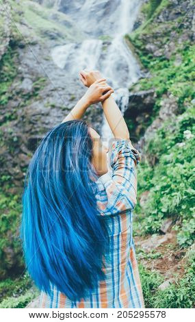 Young woman with blue hair standing with raised arms in front of waterfall in summer.