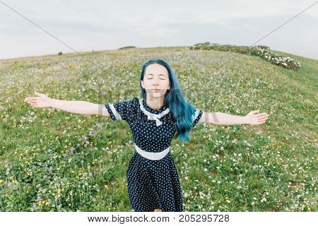 Beautiful young woman wearing in dress standing with raised arms on wildflower summer meadow front view.
