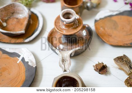 Ceramic Set Of Dishes And Cups. Decorative Potteri On The Wooden White Terble With Decorative Dried
