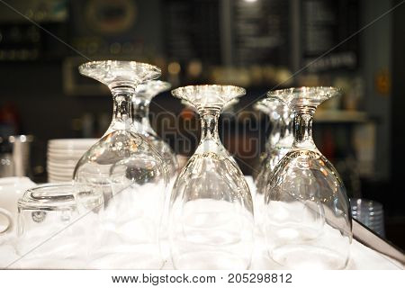 Many served wine glasses on the table turned upside-down , soft background blue