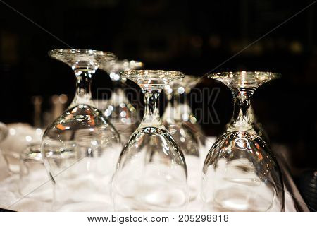 Many served wine glasses on the table turned upside-down , black background