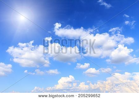 Blue sky with white clouds and sunshine on sunny summer or spring day.