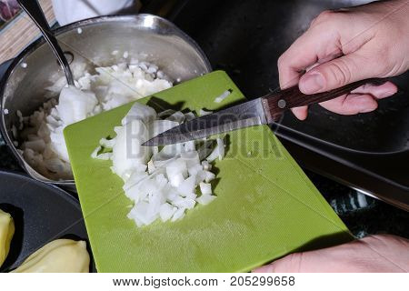 photo of female hands cutting onions on the cutting Board