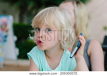 Little blond girl playing with a smartphone.