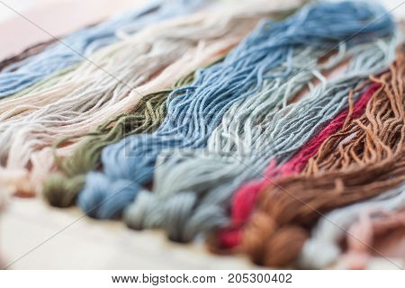 Close up set of colorful wool threads measuring tape and bobbin. Abstract hobby background