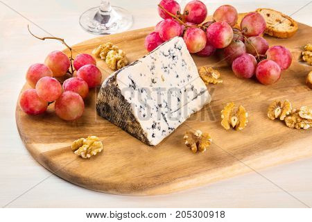A photo of a piece of Gorgonzola with vibrant grapes, slices of bread, and nuts, on a light background