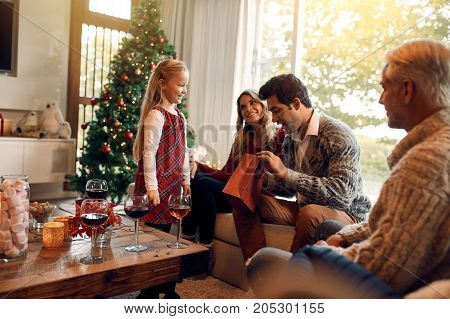 Young man opening christmas gifts from her daughter. Caucasian family sitting together in living room on a christmas eve exchanging gifts.